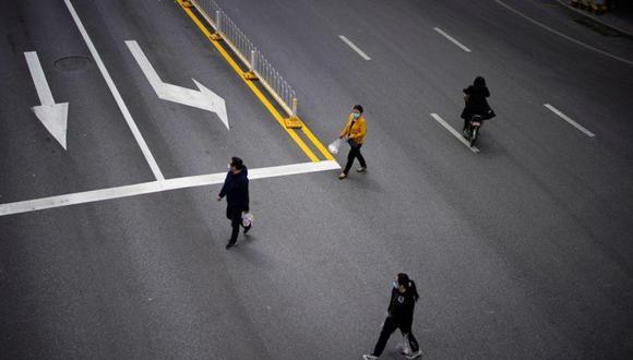 Personas con mascarillas cruzan una carretera después de que el confinamiento contra el coronavirus (COVID-19) se levantó en Wuhan, provincia de Hubei, China, el 14 de abril, 2020. REUTERS/Aly Song