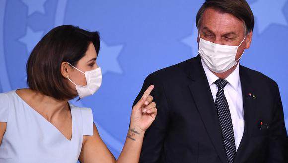 El presidente brasileño Jair Bolsonaro y la primera dama Michelle Bolsonaro hablan durante el anuncio de que el sistema público de salud cubrirá las pruebas ampliadas de punción en el talón en el Palacio Planalto, en Brasilia. (Foto: EVARISTO SA / AFP)