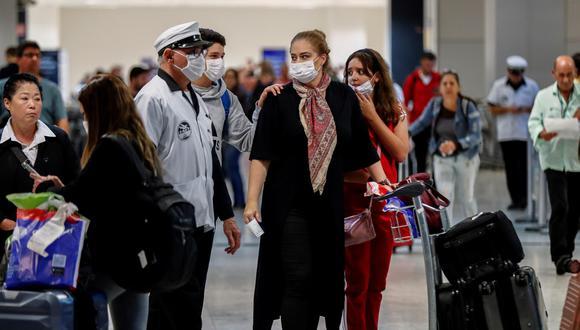 AME8495. SAO PAULO (BRASIL), 27/02/2020.- Pasajeros usan máscaras como precaución contra la propagación del nuevo coronavirus COVID-19 durante su llegada, este jueves, al Aeropuerto Internacional de Sao Paulo (Brasil). El coronavirus llegó a América Latina a través de Brasil, cuyo Gobierno confirmó este miércoles el primer caso en el país y que también supone el primero en la única región que hasta ahora permanecía ajena a esa enfermedad. EFE/ Sebastião Moreira