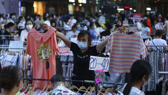 Esta foto del 8 de junio del 2020 muestra un vendedor ambulante usando mascarilla mientras ofrece prendas afuera de un mercado en Wuhan, en la provincia central de Hubei, China. (AFP)