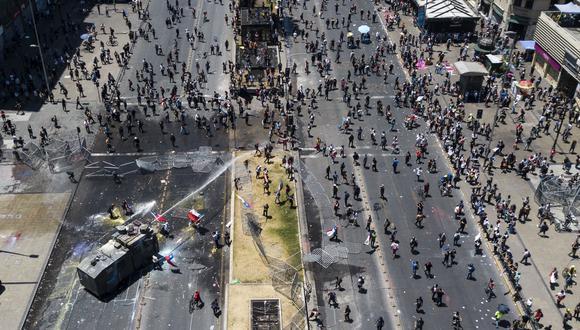 La policía usa cañones de agua para dispersar una protesta en Santiago. (AFP / JAVIER TORRES).