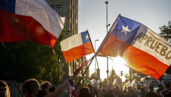 Personas con banderas chilenas participan en una manifestación en apoyo a la reforma de la constitución establecida bajo el régimen militar del general Augusto Pinochet, antes del referéndum del domingo (Foto: Martin Bernetti / AFP)