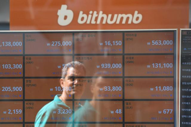 A man reflects on a screen showing the exchange rates of cryptocurrencies at the Bithumb Virtual Currency Exchange in Seoul on June 20, 2018. (Photo by Jung Yeon-je / AFP)