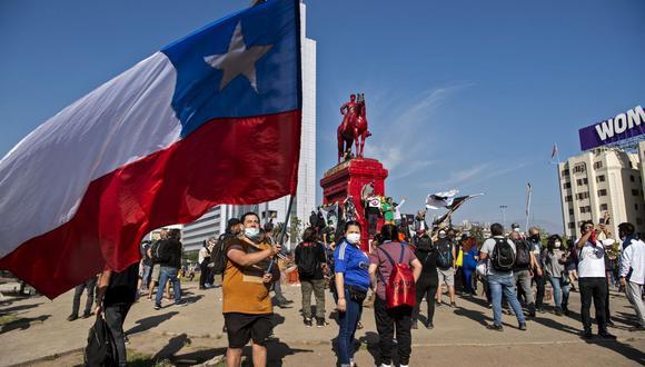 Un manifestante sostiene una bandera nacional de Chile durante una protesta contra el gobierno del presidente de Chile, Sebastián Piñera, junto al monumento al General Baquedano -pintado de rojo- en la Plaza Italia, en Santiago el 16 de octubre de 2020 (Foto de Martin Bernetti / AFP)