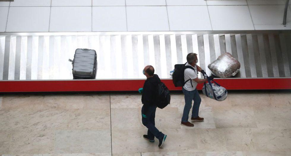 FOTO 15 | Pasajeros que acaban de aterrizar en el Aeropuerto Adolfo Suárez-Madrid Barajas (España) esperan con mascarillas a recoger sus maletas en la sala de equipaje. (Foto: Sergio Perez / Reuters).
