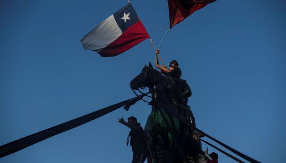Manifestantes ondean banderas de Chile hoy, durante una toma de la Plaza Italia, en las horas previas al resultado del plebiscito constitucional, en Santiago. (EFE/ Alberto Valdés).