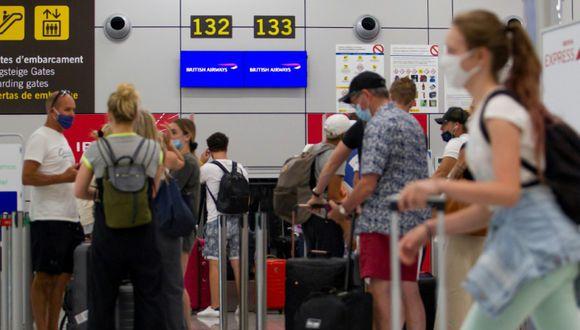 Turistas británicos aguardan para facturar en el mostrador de un vuelo a Londres el 27 de julio del 2020 en el aeropuerto de la ciudad española de Palma de Mallorca, capital de las islas Baleares. (Foto: AFP)