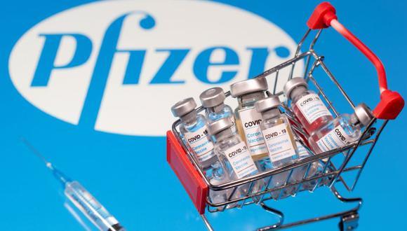 """Una pequeña canasta de compras llena de viales etiquetados como """"COVID-19 - Vacuna contra el coronavirus"""" y un símbolo médico se colocan en un logotipo de Pfizer en esta ilustración tomada el 29 de noviembre de 2020. (REUTERS/Dado Ruvic/Ilustration)."""
