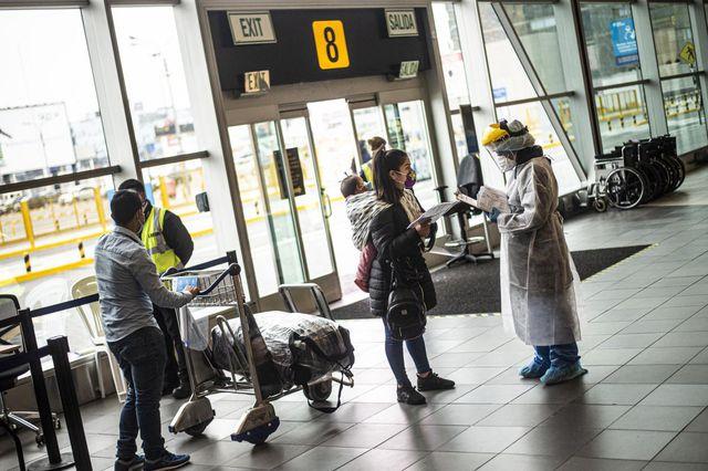 En Perú operan los vuelos domésticos y desde octubre lo harán los internacionales. En la foto, pasajeros son revisados por un trabajador de salud en el aeropuerto internacional Jorge Chávez en Lima. (Foto: Ermesto Benavides / AFP).