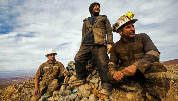 Los mineros chilenos Carlos Pacheco (izq), Hugo Moroso (centro) and Juan Bugueno (der) durante una pausa de trabajo afuera de la mina de cobre Kiara, a 136 km al sur de Antofagasta, el 22 de junio de 2021. (Foto: GLENN ARCOS / AFP).