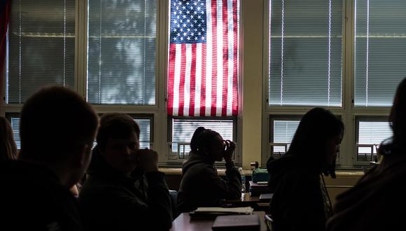 Los estudiantes de Sidney High School se sientan en clase bajo una bandera estadounidense en Ohio. (Foto: AFP).