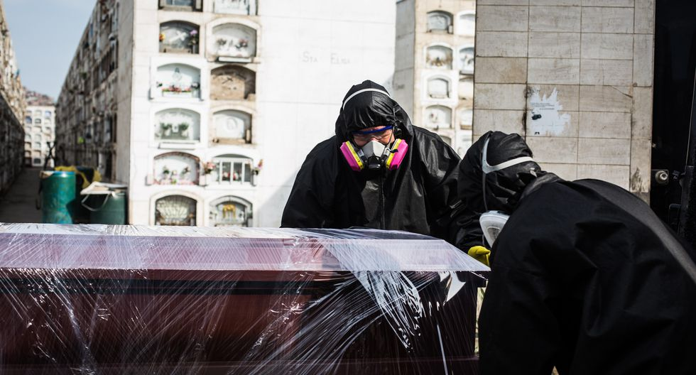 Imagen referencial muestra a trabajadores de una empresa envolviendo un féretro con papel de film en Lima (Perú). Archivo del 6 de mayo de 2020. (EFE/ Sergi Rugrand).