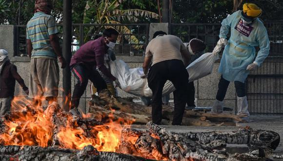 En esta fotografía tomada el 12 de mayo de 2021, un voluntario (izquierda) y familiares cargan el cuerpo de la persona que murió debido al coronavirus en un crematorio en Nueva Delhi. (Arun SANKAR / AFP).