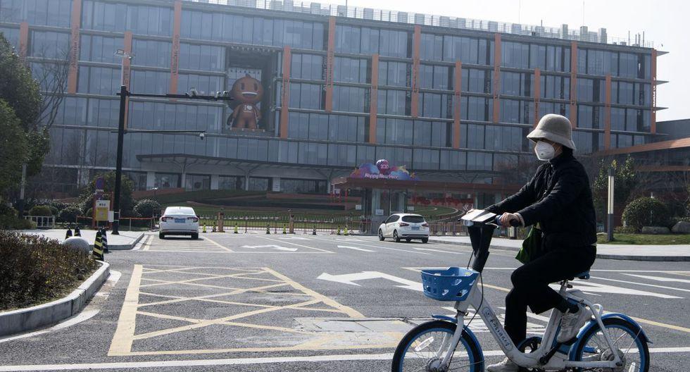 Una mujer con su mascarilla pasa en bicicleta por la sede de Alibaba en Hangzhou. (AFP).