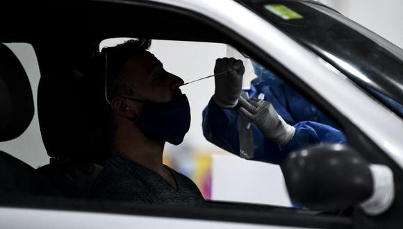 Imagen referencial. Un trabajador de salud recolecta muestras para la prueba de detección de casos de coronavirus dentro de un automóvil, en el centro de convenciones Costa Salguero, en Buenos Aires, el 5 de abril de 2021. (RONALDO SCHEMIDT / AFP).