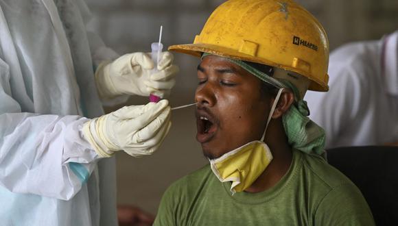 Un trabajador de la salud toma una muestra de un hisopo a una persona para una prueba de coronavirus Covid-19 en una obra de construcción en Nueva Delhi, India. (Foto de Prakash SINGH / AFP).