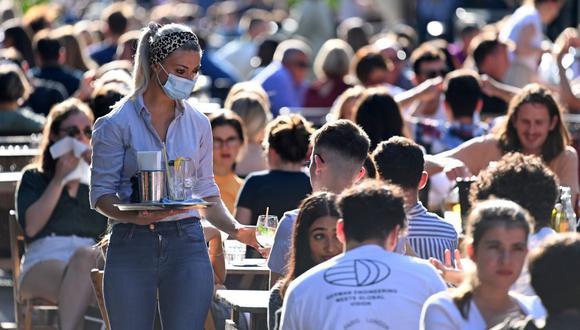 Una camarera que usa mascarilla protectora lleva bebidas a los clientes en las mesas al aire libre en Soho, en el centro de Londres, el 20 de septiembre de 2020, en pleno repunte del coronavirus. (Foto de DANIEL LEAL-OLIVAS / AFP).