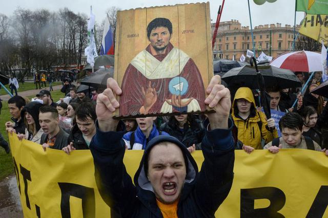 Manifestantes con una pintura que representa al fundador de Telegram, Pavel Durov, protestan contra el bloqueo de la popular aplicación de mensajería en Rusia, durante un mitin del Primero de Mayo en San Petersburgo el 1 de mayo de 2018 (Foto: OLGA MALTSEVA / AFP)