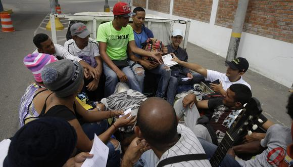 Un oficial de inmigración revisa los pasaportes de los inmigrantes venezolanos cerca de Tumbes, Perú, el 26 de agosto del 2018, mientras se sientan en la parte trasera del camión de un conductor que los recogió después de cruzar la frontera de Ecuador. (Foto: AP)