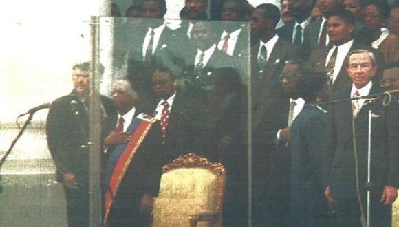 El presidente Jean-Bertrand Aristide, detrás de un vidrio de seguridad, escucha el himno nacional en las gradas del Palacio de Puerto Príncipe durante la ceremonia que marcó su retorno a Haití. (foto AFP)