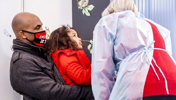 Un trabajador de salud toma una muestra de frotis de garganta de un niño para realizar una prueba del coronavirus en un centro especial de pruebas para niños en Ámsterdam, el 26 de marzo de 2021. (Remko de Waal / ANP / AFP).