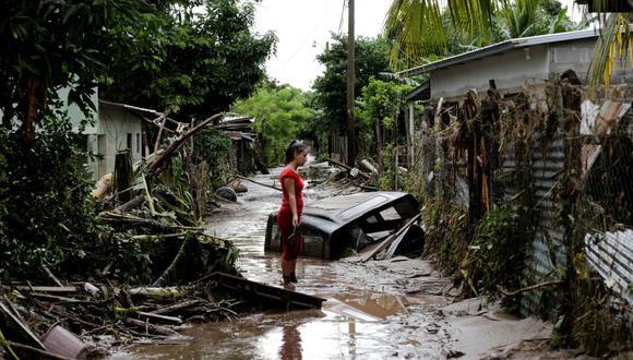 Una mujer se encuentra fuera de su casa dañada por las fuertes lluvias provocadas por el huracán Eta, en Pimienta, Honduras, el 6 de noviembre de 2020. (REUTERS/Jorge Cabrera).