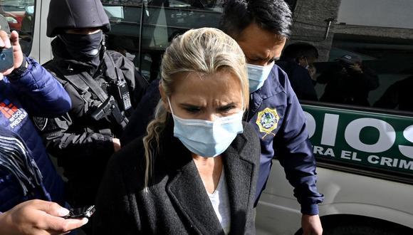 La ex presidenta interina de Bolivia Jeanine Anez (centro) es escoltada por miembros de la policía de la Fuerza Especial contra el Crimen (FELCC) luego de ser arrestada en La Paz, el 13 de marzo de 2021. (AIZAR RALDES / AFP).
