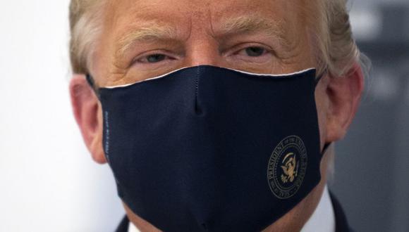 El presidente de Estados Unidos, Donald Trump, usa mascarilla mientras recorre un laboratorio donde fabrican componentes para una posible vacuna contra el coronavirus Covid-19. (JIM WATSON/AFP).