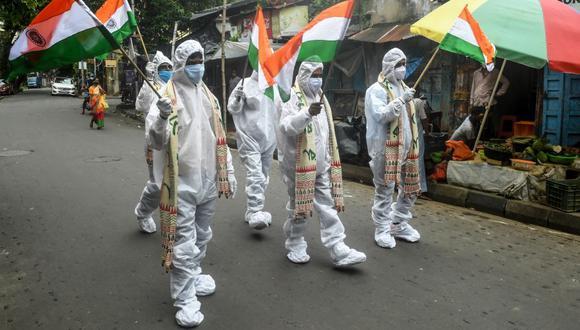 Guerreros del coronavirus COVID-19 de primera línea, como trabajadores de la salud, conductores de ambulancias, trabajadores de crematorios, vestidos con equipos de protección personal, sostienen banderas de la India como parte de las celebraciones del Día de la Independencia en Calcuta el 15 de agosto de 2020. (Foto: Dibyangshu SARKAR / AFP).