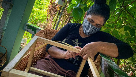 Nelsa Beaton, fabricante de muebles de mimbre, elabora una cesta de fibra, el 20 de septiembre de 2021 en su casa de La Habana. (Foto: ADALBERTO ROQUE AFP)
