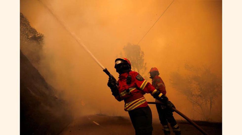 En la imagen, una pareja de bomberos intenta sofocar el incendio en el pueblo de Sandinha, cerca de Góis.