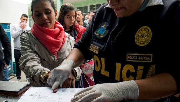 Un policía toma las huellas dactilares de un migrante venezolano mientras solicita una visa de residencia o permiso de estadía temporal en una instalación de Interpol en Lima. (Foto: AFP)