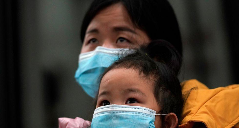 Una mujer que usa su máscara facial carga a un niño al llegar a una estación de tren en Wuhan en el primer día en el que los servicios de trenes reanudaron su servicio tras la cuarentena por coronavirus. (REUTERS / Aly Song).