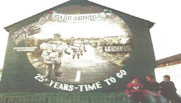 Tres niños islandeses están frente a un mural que muestra a soldados ingleses retornando a su país. El IRA anunció ayer el cese de operaciones militares (foto AFP)