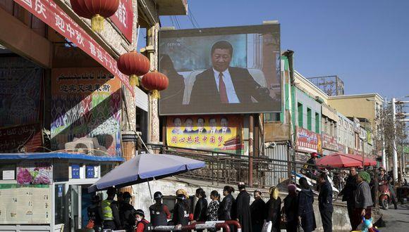 Vecinos esperando en fila en un control de seguridad en el bazar Hotan, donde una pantalla muestra al presidente de China, Xi Jinping, en Hotan, en la región occidental china de Xinjiang. (Foto: AP)