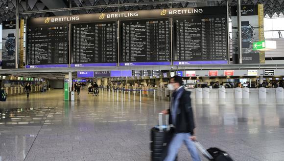 En esta foto de archivo tomada el 19 de diciembre de 2020, un pasajero camina frente a una pantalla de información gigante en el Aeropuerto Internacional de Frankfurt en Frankfurt am Main, Alemania occidental. (Armando BABANI / AFP).