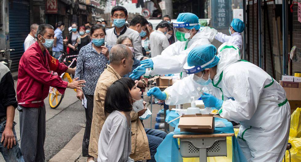 Los trabajadores médicos toman muestras de hisopos de los residentes para analizar el coronavirus COVID-19, en una calle de Wuhan. (Foto: AFP/STR)