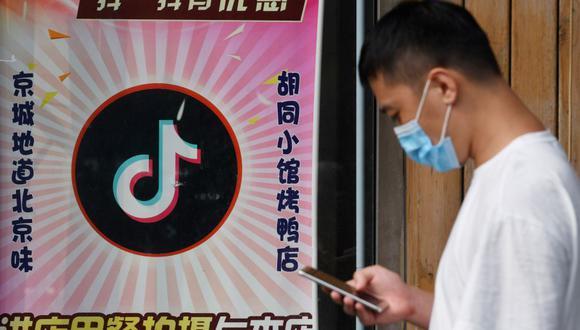 Un hombre pasa junto a un restaurante con un logotipo de TikTok en Beijing, China. (Foto de GREG BAKER / AFP).
