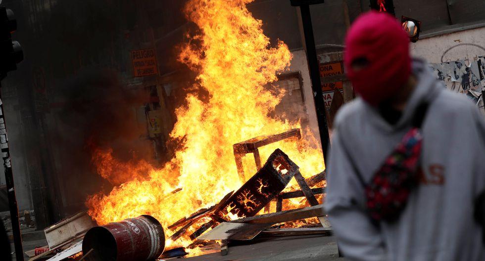 Un manifestante encapuchado pasa junto a una barricada en llamas durante una protesta en Chile. (REUTERS / Juan Gonzalez).