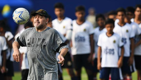 Argentine footballer Diego Maradona (L) plays the ball during a football workshop with school students in Barasat, around 35 Km north of Kolkata on December 12, 2017. Maradona is on a private visit to India. / AFP / Dibyangshu SARKAR
