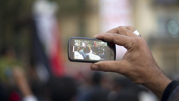 En esta foto de archivo tomada el 24 de noviembre de 2011, un hombre usa su teléfono celular para registrar la actividad de otros manifestantes antigubernamentales durante una manifestación masiva en la plaza Tahrir de El Cairo, Egipto, durante la Primavera Árabe. (Foto de Odd ANDERSEN / AFP).