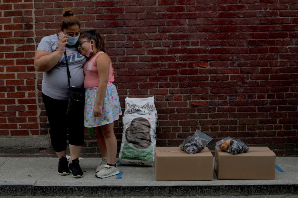 Sandra Cruz, que perdió su trabajo debido al coronavirus, se ha retrasado cuatro meses en el pago del alquiler y teme ser desalojada. En la foto espera junto a su hija tras recibir alimentos gratuitos en Chelsea, Massachusetts. (REUTERS/Brian Snyder)