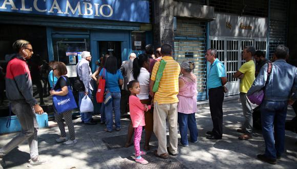 Clientes esperan fuera de una casa de cambios en Caracas, para cambiar sus dólares. (Foto: Reuters)