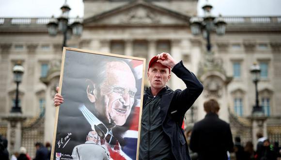 Un hombre sostiene un cartel que representa al difunto príncipe Felipe, esposo de la reina Isabel, quien murió a la edad de 99 años, en las afueras del Palacio de Buckingham en Londres, Gran Bretaña, el 10 de abril de 2021. (REUTERS/Henry Nicholls).