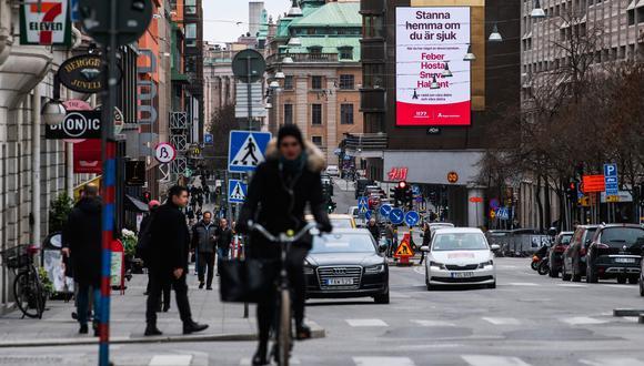 Un anuncio de los servicios de salud en las calles de Estocolmo pide a las personas que se mantengan en casa si se sienten enfermos. (AFP)