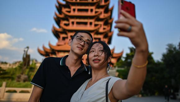 Turistas se toman un 'selfie' en la Torre Yellow Crane en Wuhan, en la provincia central china de Hubei. (Photo by Hector RETAMAL / AFP)