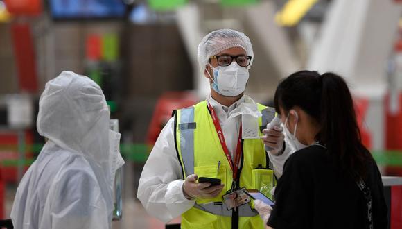 Un empleado con equipo de protección completo verifica la temperatura de los pasajeros que llegan para registrarse para su vuelo en el aeropuerto de Barajas, en Madrid, el 20 de junio de 2020. (PIERRE-PHILIPPE MARCOU / AFP).