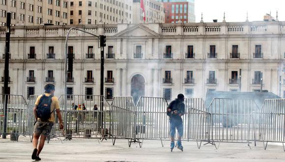 Manifestantes son alcanzados por el gas lacrimógeno de la policía antidisturbios frente al palacio de la Moneda hoy, miércoles 11 de marzo durante las protestas en conmemoración a los dos años de gobierno de Sebastián Piñera, en Santiago de Chile (Chile). EFE/Sebastián Silva