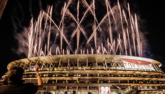 Una persona graba un video con su teléfono móvil mientras los fuegos artificiales estallan alrededor del Estadio Olímpico durante la ceremonia de clausura de los Juegos Olímpicos de Tokio 2020, este 8 de agosto de 2021. (Foto de Yasuyoshi CHIBA / AFP).