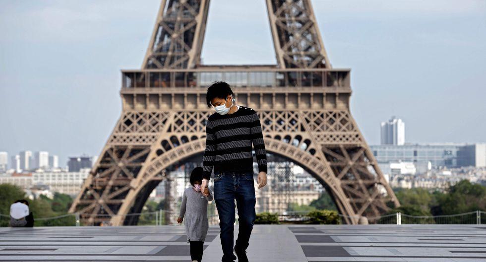 Imagen referencial de dos personas en inmediaciones de la Torre Eiffel en París. El coronavirus causó 24.594 muertos en Francia, según el último balance oficial comunicado el viernes por la noche. (AFP / THOMAS COEX).